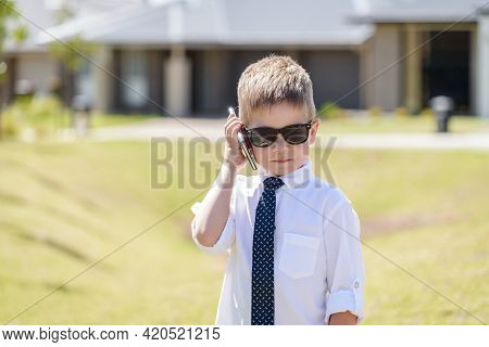 Cute Australian Boy Wearing Business Attire With Sunglasses While Using Mobile Phone On A Bright Sum