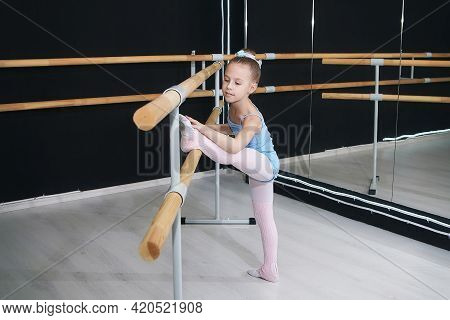 Little Girl Does Exercises In The Hall Of The Choreographic School With A Ballet Barre.