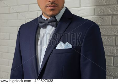 Man With Handkerchief In Breast Pocket Of His Suit Near White Brick Wall, Closeup