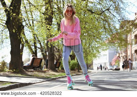 Beautiful Young Woman Roller Skating Outdoors On Sunny Day