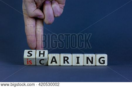Sharing Is Caring Symbol. Businessman Turns Wooden Cubes With Words 'sharing Is Caring'. Beautiful G