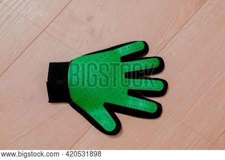Green Rubber Glove Lays On The Floor. Special Equipment. Care. Domestic Pet