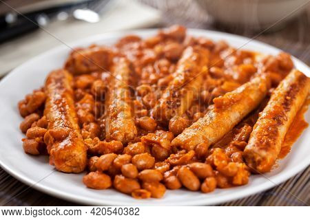 Sausage And Beans With Tomato Sauce On A Plate.