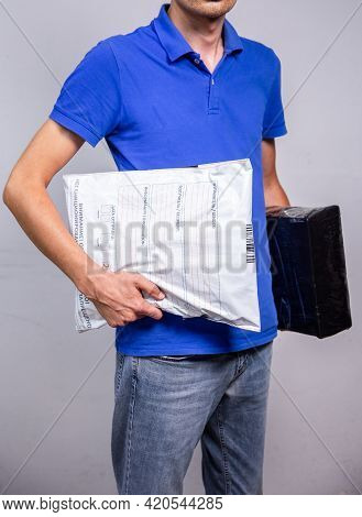 Courier With Parcels In Hand, Delivery Of Parcels By Courier To The Address.