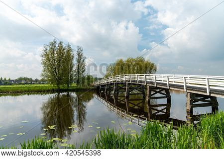 White Wooden Bridge Across A Calm Canal In Country Landscape In South Holland