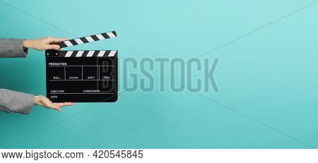 Black Clapperboard Or Movie Clapper Board For Videography With Hands In Grey Suit. It Use In Video P