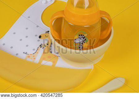 Baby Accessories On Light Yellow Background, Flat Lay. Baby Bib And Food Plate, Spoon And Baby Cup.