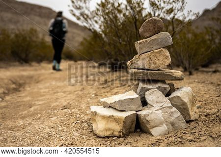 Cairn Stands Along Side Of Trail As Hiker Passes By On Dirt Trail