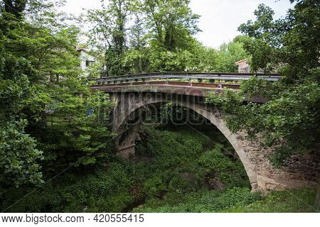 Santa Pau, Spain, May 1, 2020 - Medieval Bridge Of Old Picturesque Catalan Town. Creeping Plants On