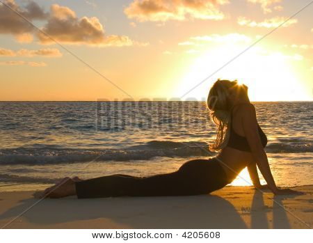 Forty Year Old Woman Doing Yoga At Sunrise On The Beach
