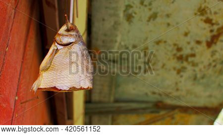 Close Up Of Dried Fish Hanging On Hook Outdoors. Piece Of Fish Being Dried On Hook