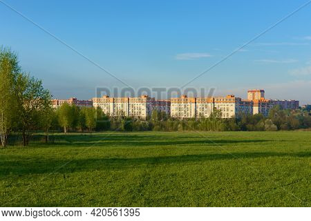 Panorama A Park Scene With A Green Grass Field, A Tree Plant And A Multi-storey Residential Complex