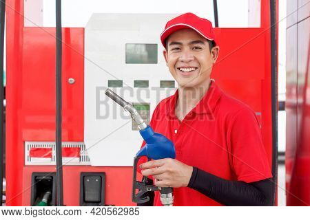 Asian Gas Station Attendant In Red Uniform Stand Smiling, Holding Gas Pump Nozzle At The Gas Station