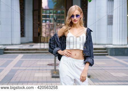 Young Beautiful Woman Of Kakaz Nationality Poses In The Afternoon On The Street Of The City In A Whi