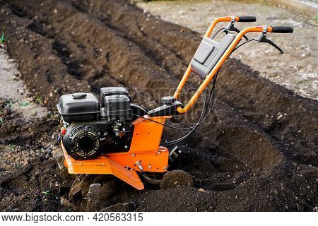 Motor Cultivator For Digging Up The Earth. Spring Planting And Digging In The Damp Earth. Garden And