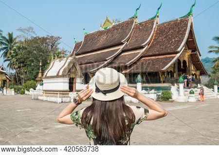 Back View Of Woman Tourist Visiting Wat Xieng Thong An Iconic Temple In Luang Prabang, The Unesco Wo