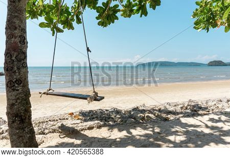 Wooden Swing Hanging On The Tree On Brow Sand Beach, Blue Sea Under Blue Sky On Background