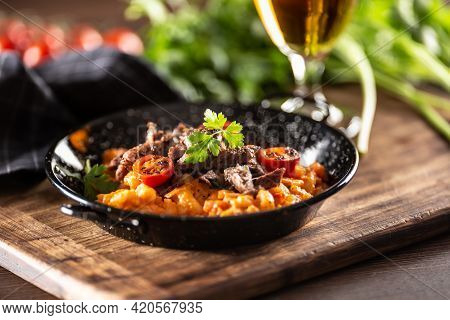Tomato Sauce Gnocchi With Sous-vide Beef And Fresh Tomatoes Served In A Dark Plate.