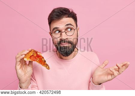 Hesitant Bearded Young Man Shrugs Shoulders Holds Tasty Pizza Being Unaware Looks Clueless Away Dres
