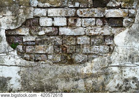 A Heavily Weathered And Textured Brick Wall Beneath Broken Plaster. Aged Bricks Are Exposed Beneath