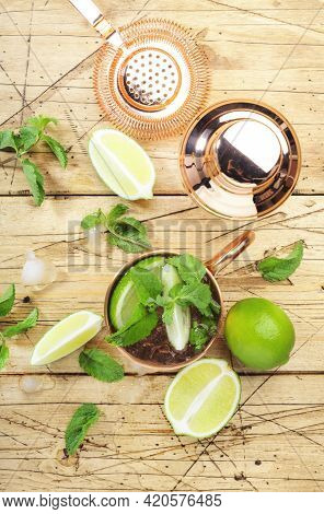 Moscow Mule Alcoholic Cocktail In Copper Mug With Lime, Ginger Beer, Vodka And Mint. Wooden Bar Coun