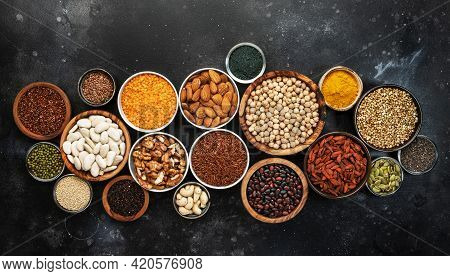 Selection Of Superfoods, Legumes, Cereals, Nuts, Seeds In Bowls On Black Background. Superfood As Ch