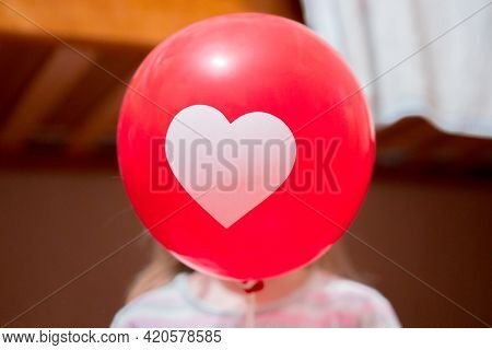 Kid Holds A Red Balloon With Drawn Heart In Front Of Her Face. Love. Care. Family. Relationship. Hom