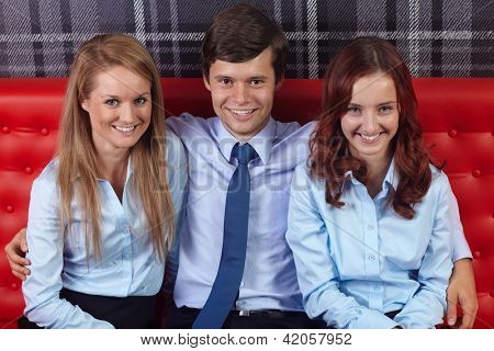 Young attractive happy smiling businesswomen and businessman sitting together