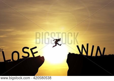 Silhouette Man Jumping From Lose Cliff To Win Cliff With Sun And Sky , Business And Investment Conce