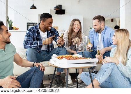 Group Of Diverse Male And Female Friends Eating Pizza At Home, Drinking Beer, Having Conversation On