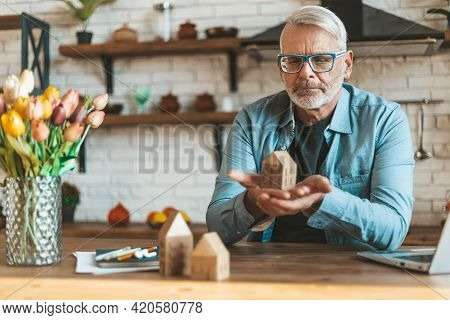 Preservation And Restoration Of Real Estate. A Mature Man Holds A Model Of A House In His Hands. Ref