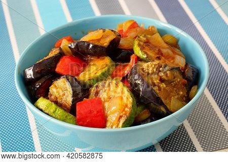 Ratatouille. Vegetable Stew With Eggplant, Zucchini And Bell Peppers In A Blue Bowl