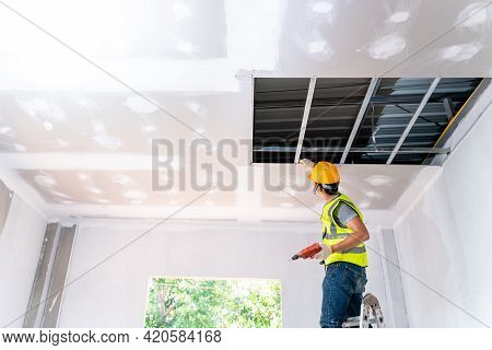 Asian Construction Worker Assemble A Suspended Ceiling With Drywall And Fixing The Drywall To The Ce