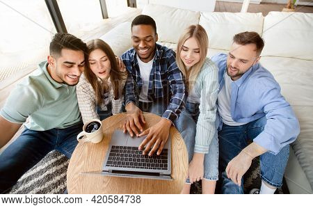 Positive Multiethnic Friends Using Laptop At Home, Making Video Call, Watching Movie Together, Brows
