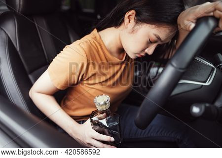Drunk Female Driver In Car, Bottle Of Alcohol In A Woman's Hand Behind The Steering Wheel - A Concep