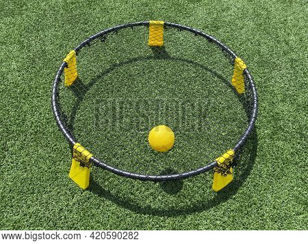 A Close Up Of A Yellow And Black Spike Ball Game Set Up On A Green Turf Field With The Yellow Ball O