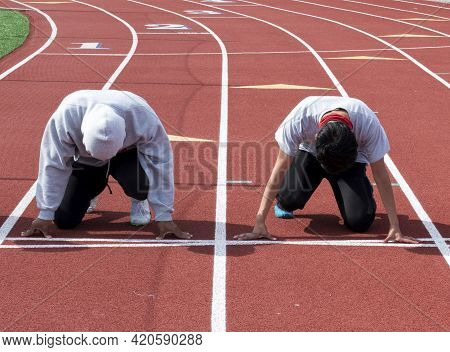 Front View Of Two High School Boy Sprinters Ready On Their Mark To Run A Sprint Race Against Each Ot