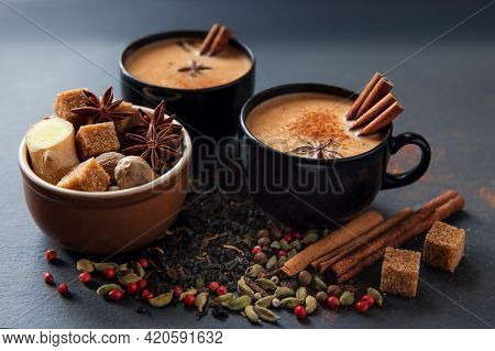 Masala Tea Traditional Hot Indian Sweet Milk Spiced Drink In Black Cups. Spices Cinnamon Sticks, Car