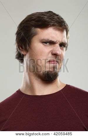 Portrait of young man with repulsion expression  isolated over background