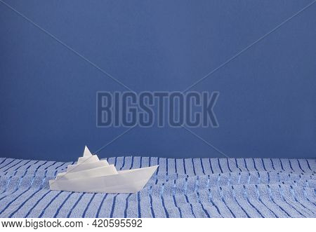 White paper ship on blue towel waves abstract concept photo of wide sea or ocean on blue copy space background