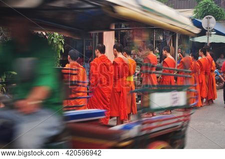 Tradition Of Almsgiving With Sticky Rice By Monks Laotian Procession Walk On The Road For Lao People