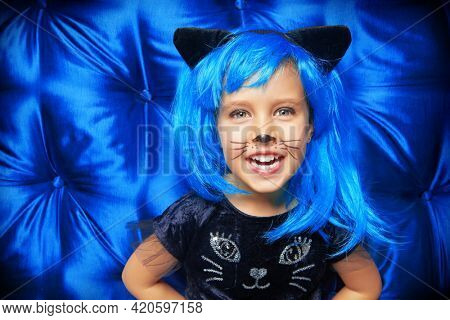 Carnival kitty costume. Cute cheerful  little girl child in cat costume and bright blue wig laughing at camera with joy. Halloween party.