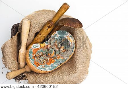 Orange Moldy Cut Of A Pumpkin Surrounded By Kitchen Utensils On Sackclothon A White Background, Mold