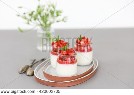 Italian Dessert Panna Cotta With Fruit Jelly And Fresh Pieces Of Strawberries On Gray Background. Co