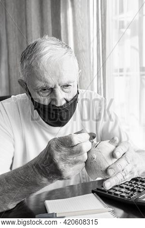 Old Man In A Medical Mask Counts Pennies From The Pension Fund. A Worried Elderly Man Puts Money In