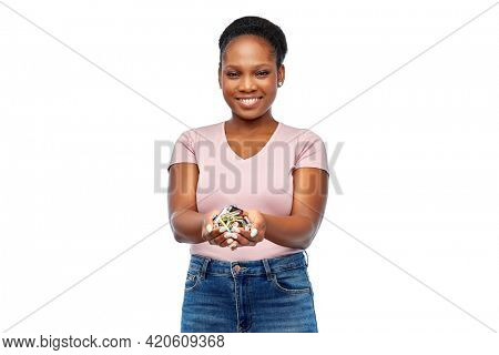 recycling, waste sorting and sustainability concept - happy smiling young african american woman holding alkaline batteries over white background