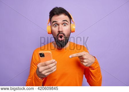 Impressed Stunned Man With Thick Beard Indicates At Smartphone Display Being Amazed By Stunning News