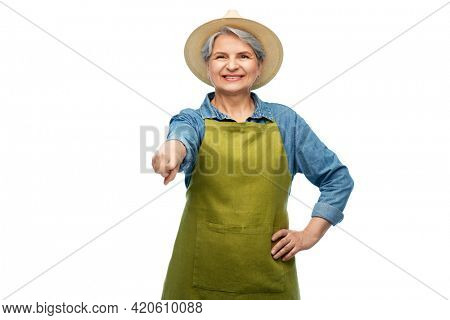 gardening, farming and old people concept - portrait of smiling senior woman in green garden apron and straw hat pointing finger to camera over white background