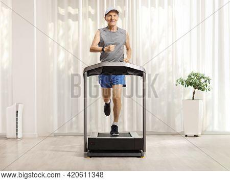 Full length portrait of an elderly man running on a treadmill at home