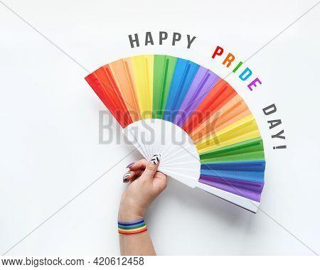 Lgbtq Community Pride. Hand Holds. Rainbow Fan. Ribbon With Rainbow Design On Wrist. Flat Lay, Top V